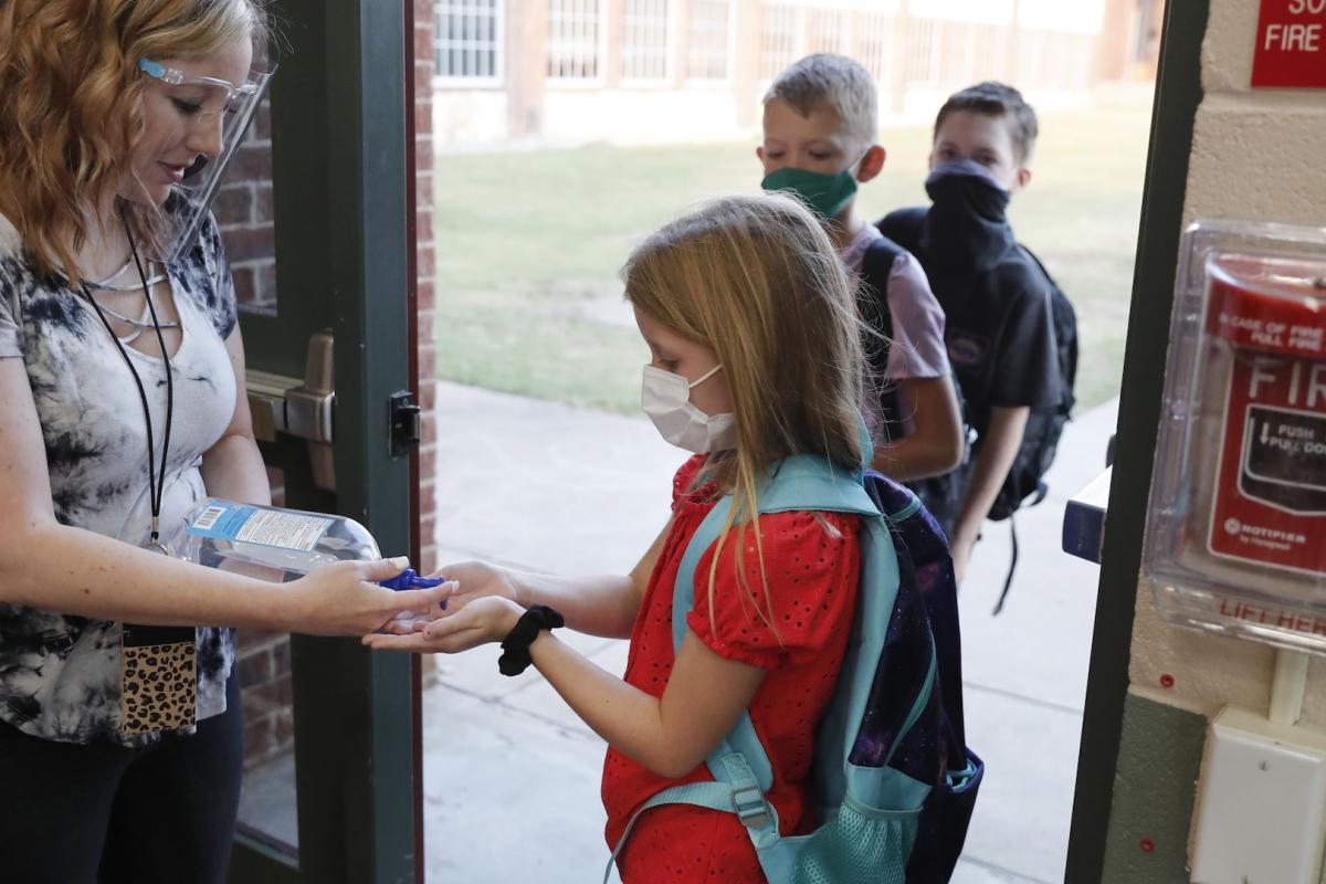 In this Aug. 5, 2020, file photo, wearing masks to prevent the spread of COVID19, elementary school students use hand sanitizer before entering school for classes in Godley, Texas. (AP Photo/LM Otero, File)