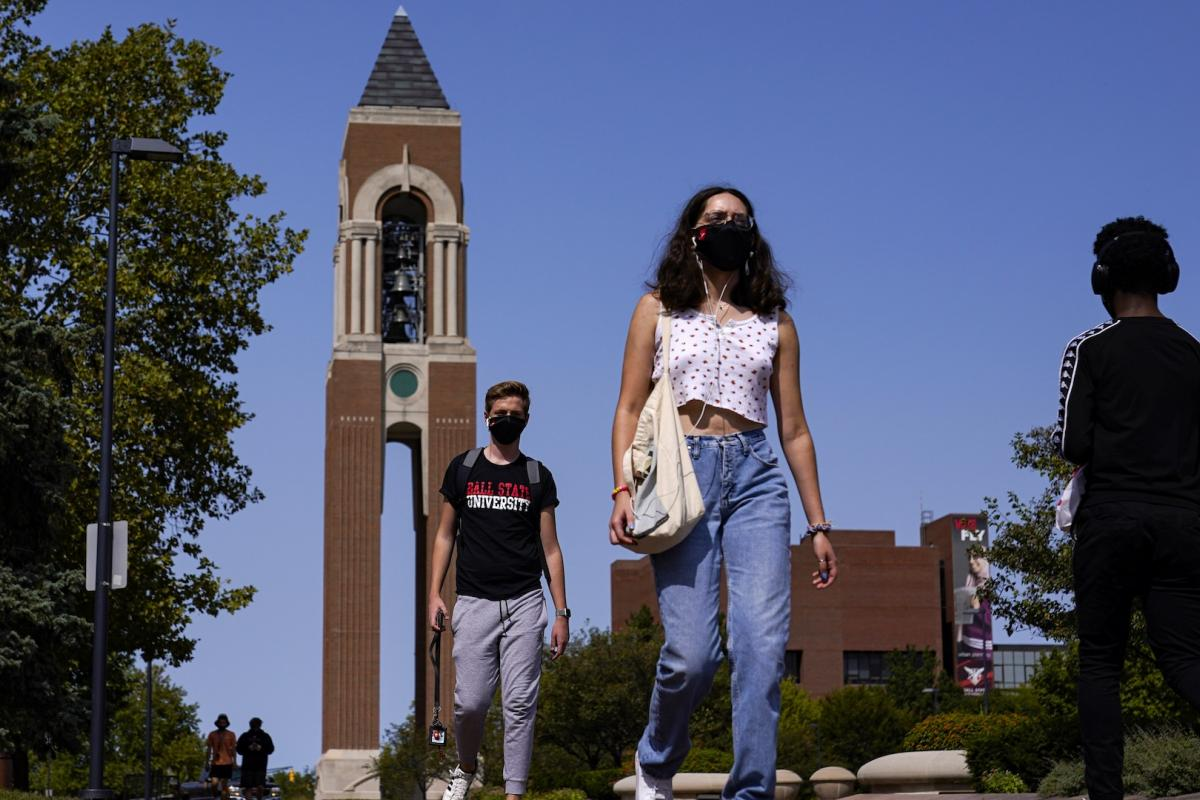 Masked students walk through the campus of Ball State University in Muncie, Ind., Thursday, Sept. 10, 2020. College towns across the U.S. have emerged as coronavirus hot spots in recent weeks as schools struggle to contain the virus. (AP Photo/Michael Conroy)