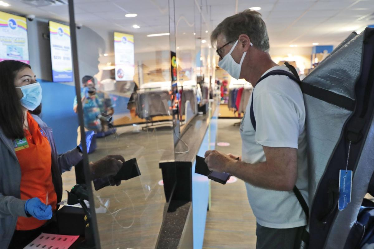 Amid concerns of the spread of COVID-19, a cashier and customer are separated by plexiglass at the city owned waterpark in Grand Prairie, Texas, Friday, May 29, 2020. Water parks in Texas were allowed to reopen today. (AP Photo/LM Otero)