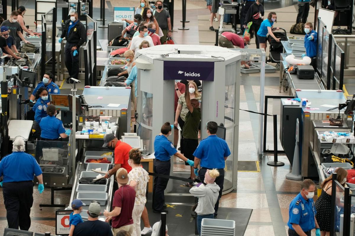 Travelers wear face coverings in the line for the south security checkpoint in the main terminal of Denver International Airport on Aug. 24, 2021, in Denver. (AP Photo / David Zalubowski)