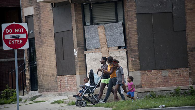 A group of girls walk in Englewood. This building is across the street from one of 50 Chicago Public Schools that closed in 2013. (Photo by Bill Healy)
