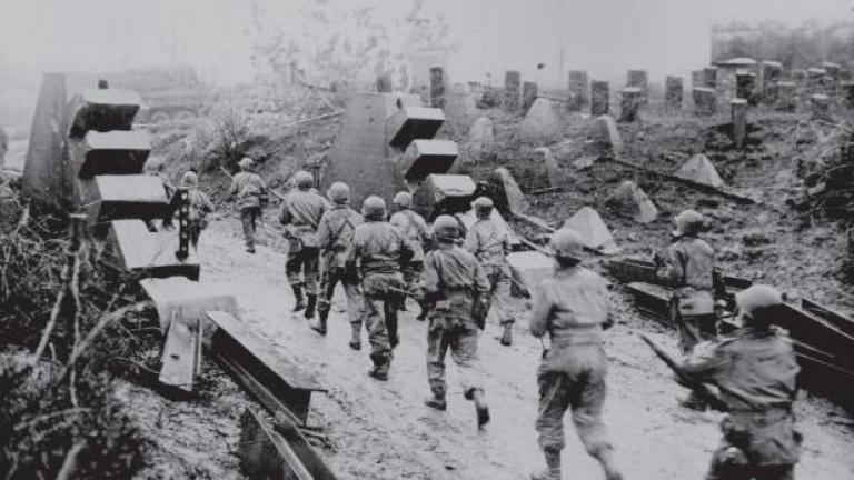 US Infantry advancing through a hole blasted in the Siegfried Line, or Westall, in October 1944. (Viking Penguin)