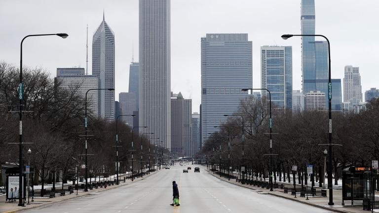An elderly woman walks across the usually busy Columbus Drive that splits Chicago's Grant Park in half, on the first work day since Illinois Gov. J.B. Pritzker gave a shelter in place order last week, Monday, March 23, 2020, photo, in Chicago. (AP Photo / Charles Rex Arbogast)