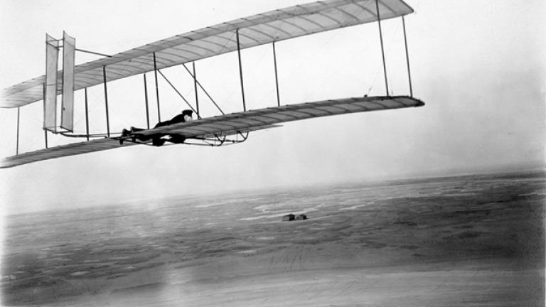Wilbur takes wing in the 1902 glider soon after the brothers' return to Kitty Hawk in 1903. Their camp and shed stand alone in the distant wind-swept sands. Courtesy of Special Collections and Archives, Wright State University.