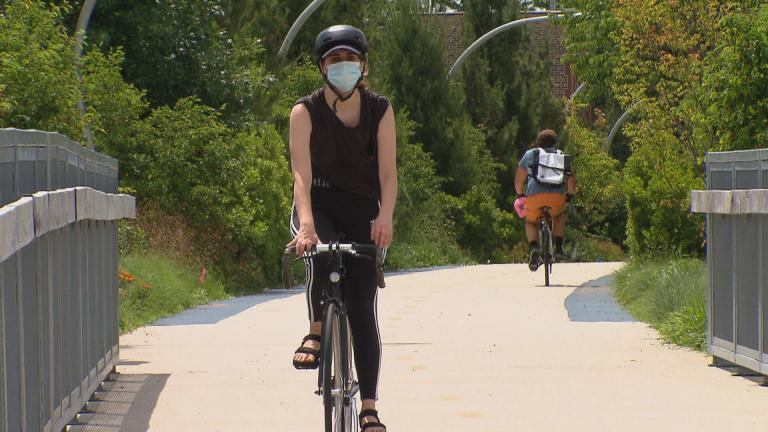 A cyclist wearing a mask rides along the 606 trail in Chicago. (WTTW News)