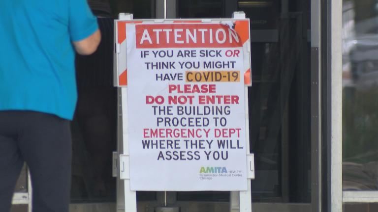 A sign directs patients with COVID-19 symptoms to the emergency department at AMITA Health Resurrection Medical Center Chicago on Tuesday, May 26, 2020. (WTTW News)