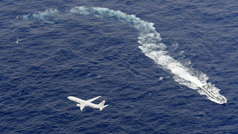 In this Dec. 6, 2018, file photo, Japan's Coast Guard ship, top, and U.S. military plane are seen at sea off Kochi, southwestern Japan, during a search and rescue operation for missing crew members of a U.S. Marine refueling plane and fighter jet. (Kyodo News via AP, File)