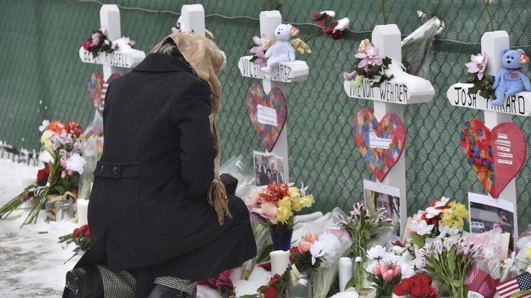 Mourners place flowers at the crosses outside of the Henry Pratt Co. in Aurora, Illinois, on Sunday, Feb. 17, 2019, in memory of the five employees killed on Friday. (Jeff Knox / Daily Herald via AP)