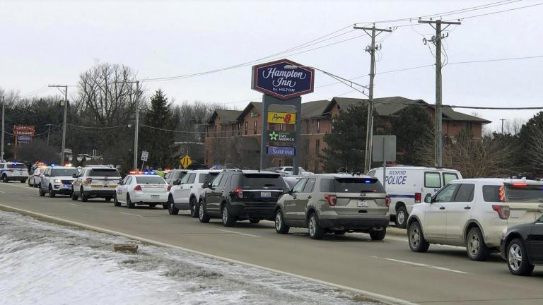 Area law enforcement vehicles gather near the scene of a shooting in Rockford, Ill., Thursday, March 7, 2019. (Ken DeCoster / Rockford Register Star via AP)
