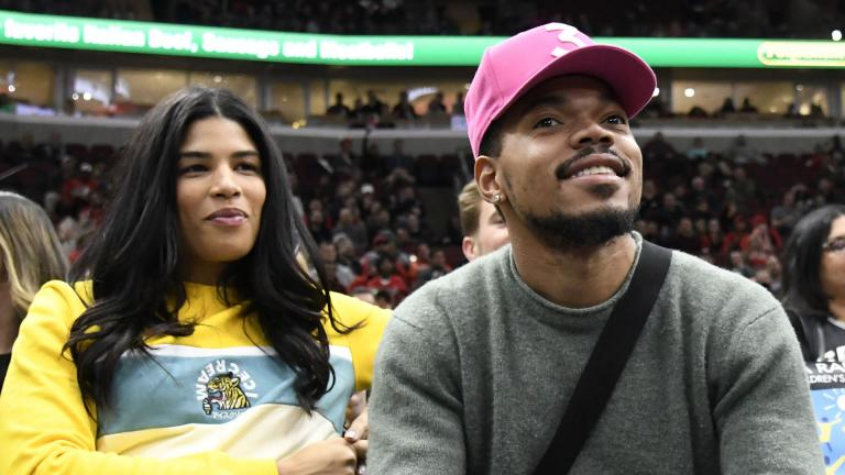 In this Nov. 26, 2018 file photo, Chance the Rapper, right, and Kirsten Corley appear during the second half of an NBA basketball game between the Chicago Bulls and the San Antonio Spurs in Chicago. (AP Photo / David Banks, File)
