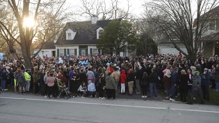 "Mourners gather outside the home of 5-year-old Andrew ""AJ"" Freund for a vigil Wednesday, April 24, 2019, in Crystal Lake, Ill. Andrew's body was found in a wooded area in Woodstock Wednesday, and the boy's parents have been charged with his murder. (John J. Kim/Chicago Tribune via AP)"