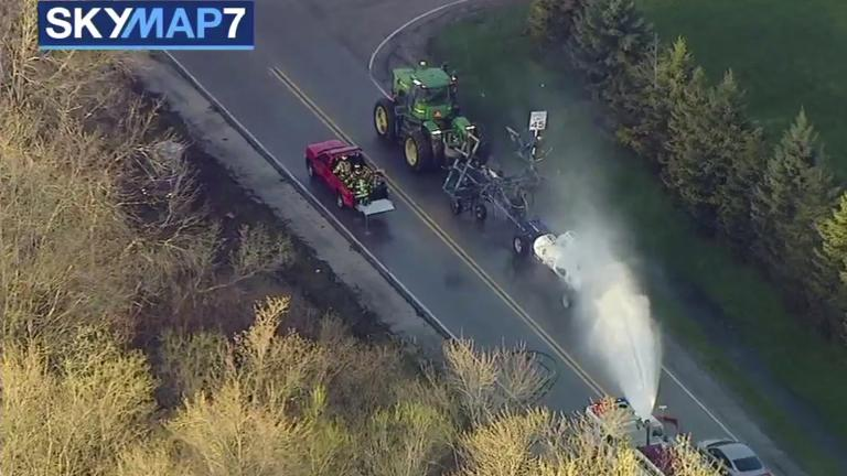 In this still image from video provided by ABC7 Chicago, a fire engine sprays water on a container of the chemical that farmers use for soil after anhydrous ammonia leaked Thursday, April 25, 2019, in Beach Park, Illinois. (ABC7 Chicago via AP)