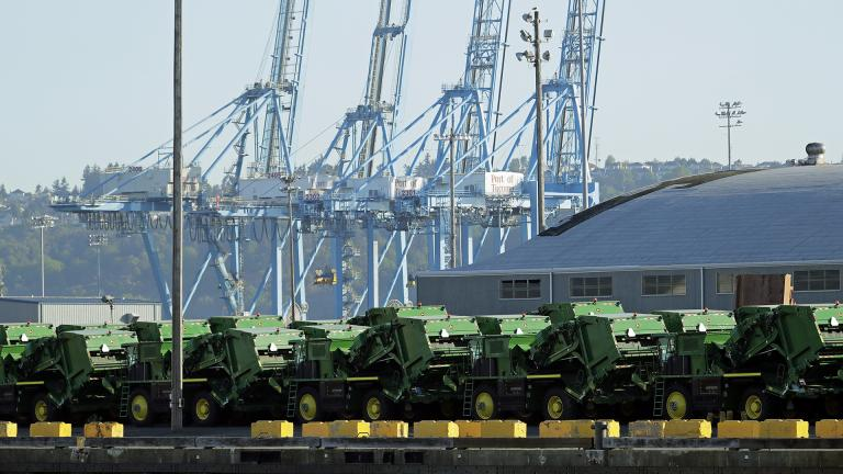 In this May 10, 2019, file photo John Deere Agricultural machinery made by Deere & Company sits staged for transport near cranes at the Port of Tacoma in Tacoma, Washington. (AP Photo / Ted S. Warren, File)