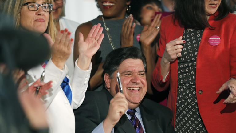 Illinois Gov. J.B. Pritzker signs the Reproductive Health Act into law with bill sponsors Illinois State Senator Melinda Bush, left, and Illinois State Rep. Kelly Cassidy, right, at the Chicago Cultural Center on Wednesday, June 12, 2019. (Jose M. Osorio / Chicago Tribune via AP)