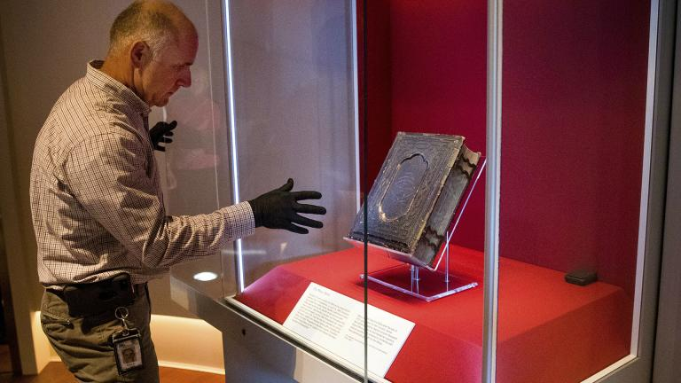 Mike Casey, exhibits project manager at the Abraham Lincoln Presidential Museum, moves the newly acquired Bible that belonged to Abraham Lincoln in his final year of life, into an exhibit at the museum following a press conference announcing its arrival Thursday, June 20, 2019, in Springfield, Illinois. (Ted Schurter / The State Journal-Register via AP)