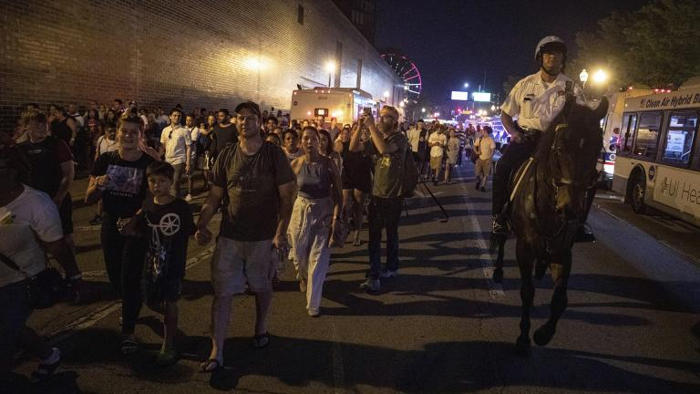 In this Thursday, July 4, 2019 photo, A Chicago Police Department officer guards people as they stream out of Chicago's Navy Pier after reports of stabbings and threatening injuries after the 4th of July celebrations. (AP Photo / Amr Alfiky)