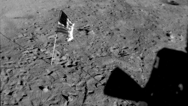This July 21, 1969 photo made available by NASA shows the U.S. flag planted at Tranquility Base on the surface of the moon, and a silhouette of a thruster at right, seen from a window in the Lunar Module. (NASA via AP)