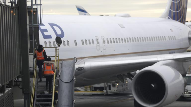 In this Jan. 23, 2019, photo employees walk up a ramp toward a ramp where a United Airlines jet is parked at a gate Newark Liberty International Airport in Newark, New Jersey. (AP Photo / Julio Cortez)