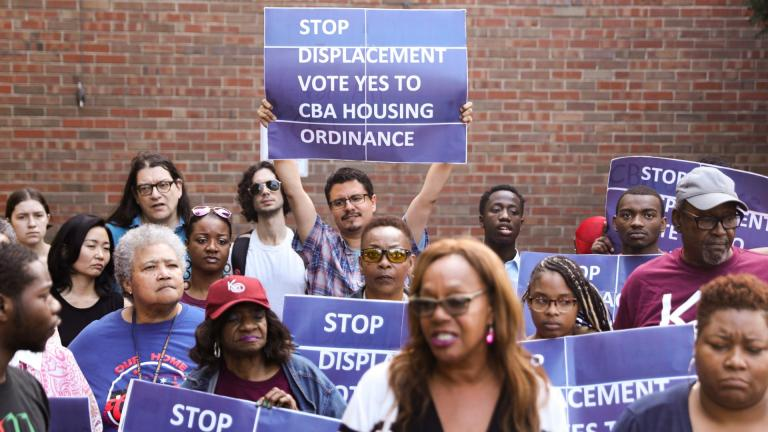 In this Tuesday, July 23, 2019 photo, activist Jose Reuena, center in back row, holds a placard during a news conference and rally in Chicago. (AP Photo / Amr Alfiky)