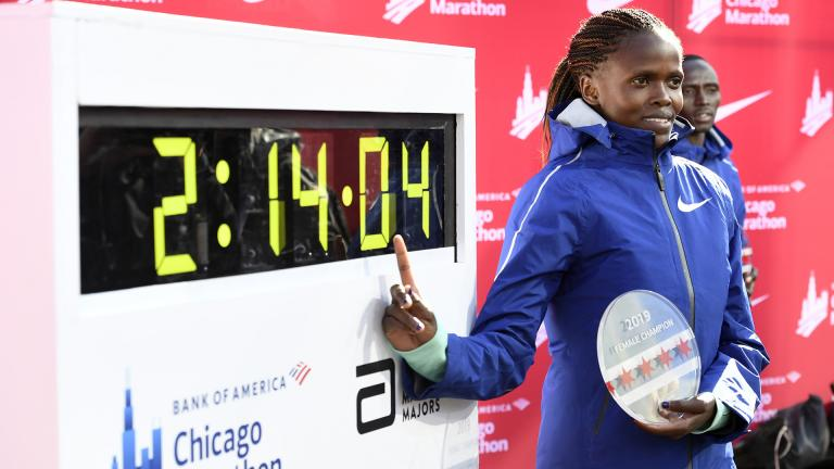 Brigid Kosgei of Kenya, poses with her time after winning the Women's Bank of America Chicago Marathon while setting a world record of 2:14:04, Sunday, Oct. 13, 2019, in Chicago. (AP Photo / Paul Beaty)