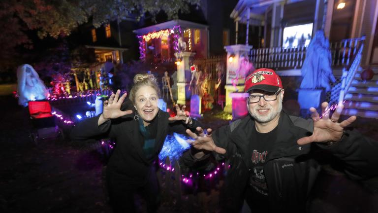 In this Tuesday, Oct. 29, 2019 photo, neighbors Beth LeFauve, left, and Nelson Gonzalez pose for a portrait outside their two Bernard Street homes and the Halloween decorations spanning both properties in Chicago. (AP Photo / Charles Rex Arbogast)