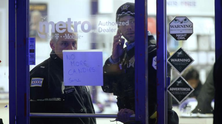 A police supervisor and officer stand inside a cell phone store in the 3700 block of West 26th Street, where a 7-year-old girl was shot while trick-or-treating Thursday, Oct. 31, 2019, in Chicago. (John J. Kim / Chicago Tribune via AP)