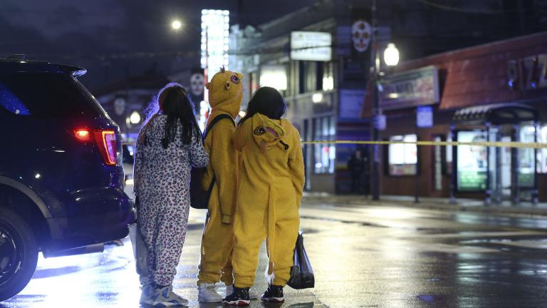 A group of children view a crime scene, where a 7-year-old girl was shot while trick-or-treating Thursday, Oct. 31, 2019, in Chicago. (John J. Kim / Chicago Tribune via AP)
