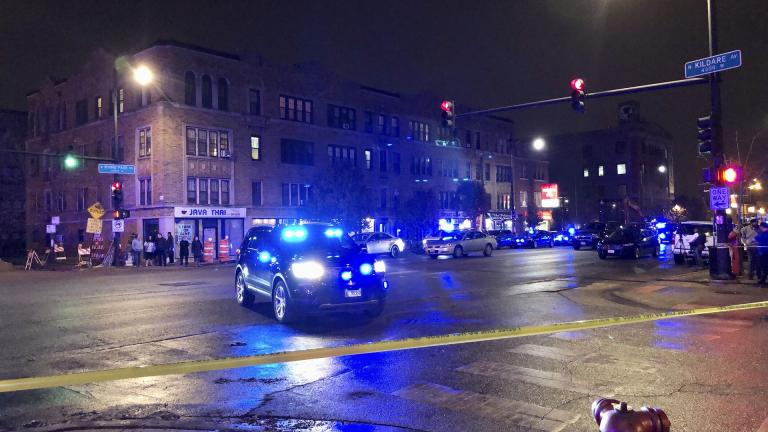 Chicago Police investigate the scene where an officer was shot by a suspected bank robber in Chicago, Tuesday night, Nov. 19, 2019. A 15-year-old boy was also wounded in the shooting, while the suspect was shot and killed. (Sam Charles / Chicago Sun-Times via AP)