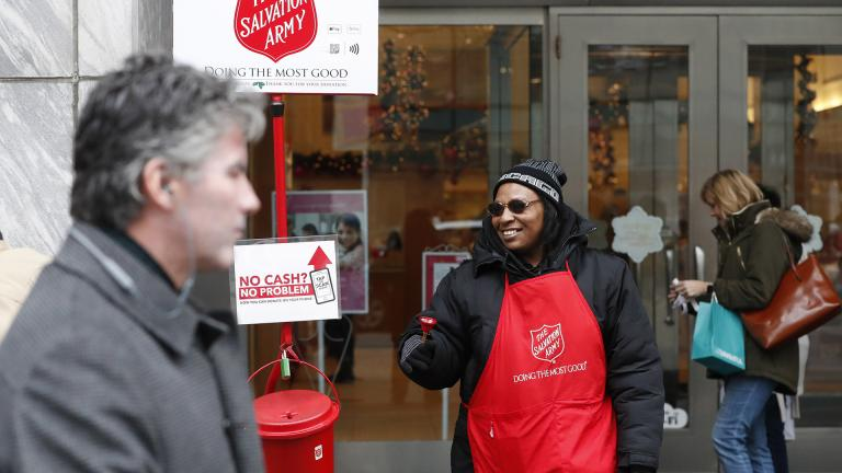 In this Friday, Nov. 15, 2019, photo, bell ringer Carolyn Harper encourages people to donate to the Salvation Army's annual holiday red kettle campaign on Chicago's Magnificent Mile. (AP Photo / Charles Rex Arbogast)