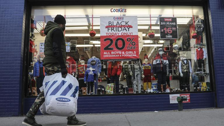 In this Nov. 29, 2019, file photo people walk by a Black Friday promotional at Cookie's department store in the Brooklyn Borough of New York. (AP Photo / Bebeto Matthews, File)