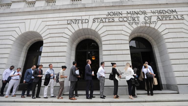 In this Tuesday, July 9, 2019 file photo, people wait in line to enter the 5th Circuit Court of Appeals to sit in overflow rooms to hear arguments in New Orleans. (AP Photo / Gerald Herbert, File)