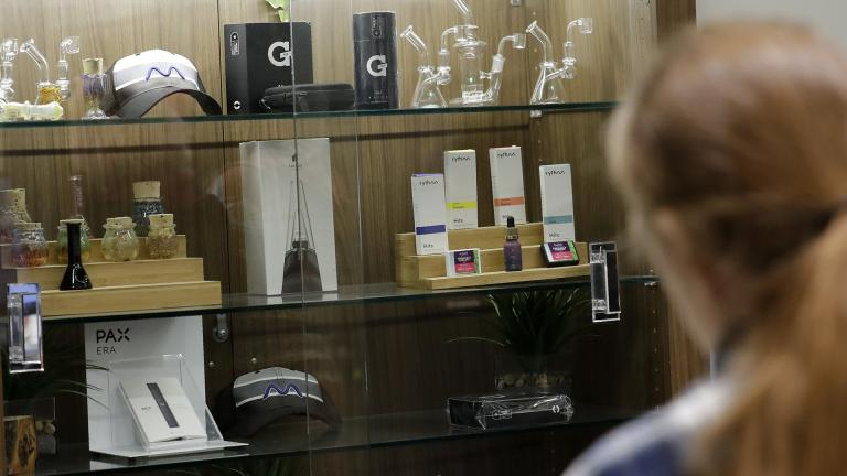 In this Thursday, Dec. 26, 2019 photo, a registered medical marijuana patient looks at products at the Rise cannabis store in Mundelein, Illinois. Starting Jan. 1, 2020, Illinois will join Michigan as the only Midwestern states broadly allowing the sale and use of marijuana. (AP Photo / Nam Y. Huh)