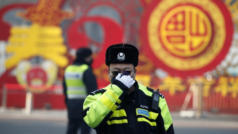 A traffic policeman adjusts his mask on a street in Beijing, Sunday, Feb. 9, 2020. (AP Photo / Andy Wong)