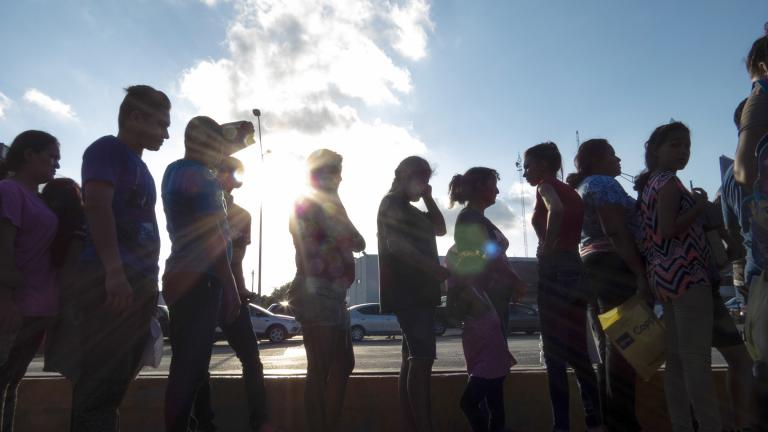 In this Oct. 5, 2019 file photo, migrants seeking asylum wait in line with their case paperwork during a weekly trip by volunteers, lawyers, paralegals and interpreters to the migrant campsite outside El Puente Nuevo in Matamoros, Mexico. (Denise Cathey / The Brownsville Herald via AP, File)