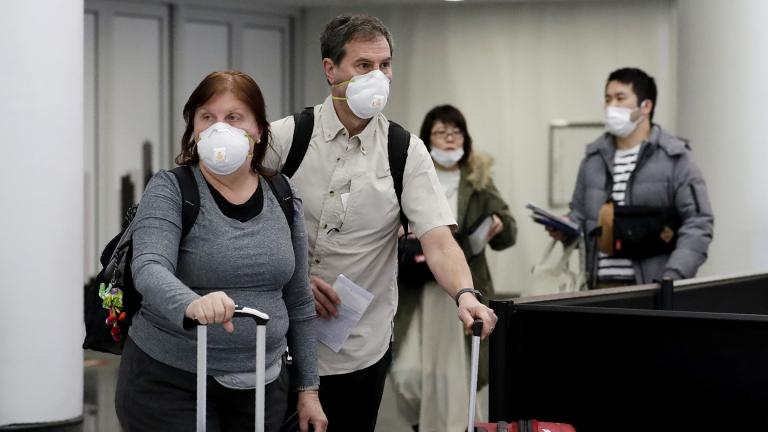 Travelers wear protective mask as they walk through in terminal 5 at O'Hare International Airport in Chicago, Sunday, March 1, 2020. (AP Photo / Nam Y. Huh)