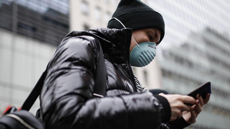 Pedestrian uses her phone while wearing a face mask in Herald Square, Thursday, March 12, 2020, in New York. (AP Photo / John Minchillo)