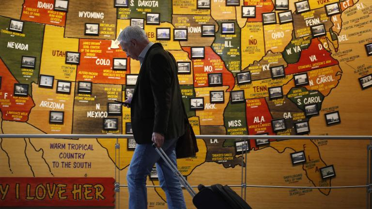 In this March 18, 2020 photo, a traveler checks his mobile telephone while passing a map of the United States on the way to the security checkpoint in the main terminal in Denver International Airport. (AP Photo / David Zalubowski)