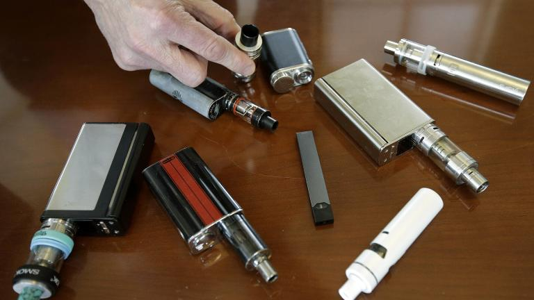 In this Tuesday, April 10, 2018 photo, a high school principal displays vaping devices that were confiscated from students at the school in Massachusetts. (AP Photo / Steven Senne)