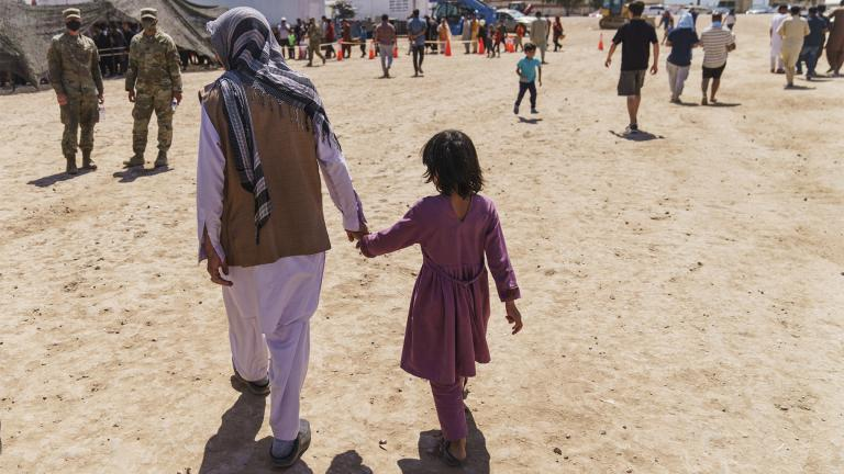 A man walks with a child through Fort Bliss' Doña Ana Village where Afghan refugees are being housed, in New Mexico, Friday, Sept. 10, 2021.