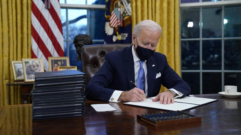 President Joe Biden signs his first executive order in the Oval Office of the White House on Wednesday, Jan. 20, 2021, in Washington. (AP Photo / Evan Vucci)