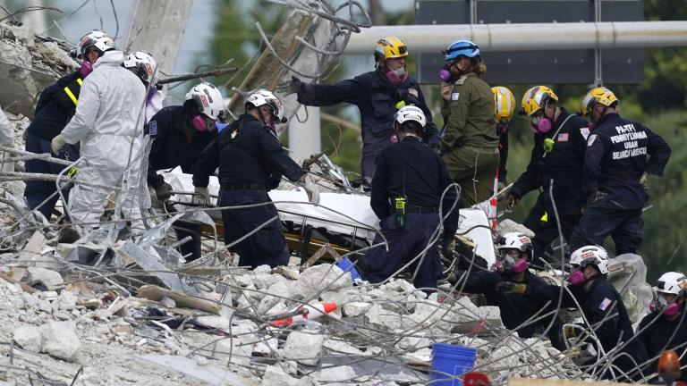 Rescue workers move a stretcher containing recovered remains at the site of the collapsed Champlain Towers South condo building, Monday, July 5, 2021 in Surfside, Fla. (AP Photo / Lynne Sladky)