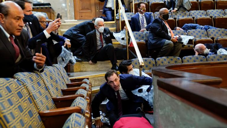 People shelter in the House gallery as protesters try to break into the House Chamber at the U.S. Capitol on Wednesday, Jan. 6, 2021, in Washington. (AP Photo / Andrew Harnik)