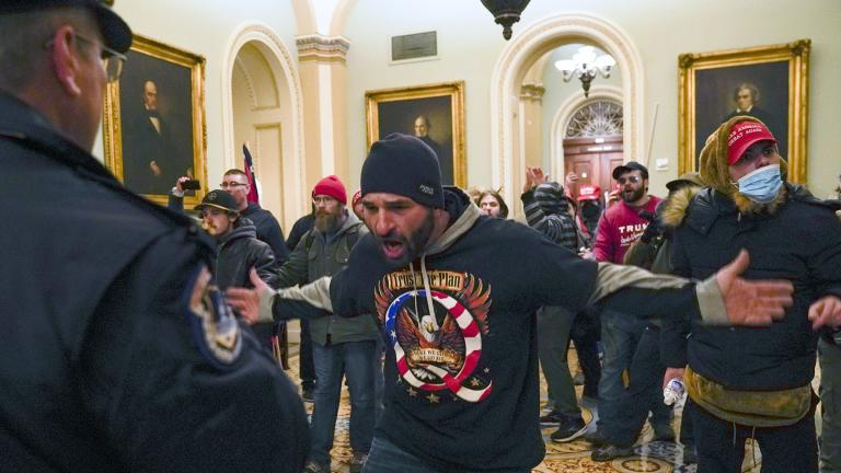 Protesters gesture to U.S. Capitol Police in the hallway outside of the Senate chamber at the Capitol in Washington, Wednesday, Jan. 6, 2021, near the Ohio Clock. (AP Photo / Manuel Balce Ceneta)