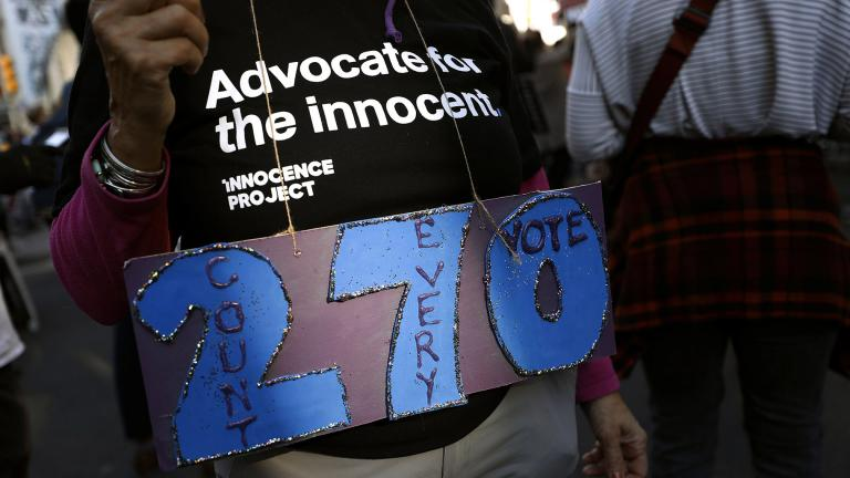 A person holds a sign referring to the number of electoral votes needed to win the presidency while demonstrating outside the Pennsylvania Convention Center where votes are being counted, Thursday, Nov. 5, 2020, in Philadelphia, following Tuesday's election. (AP Photo / Rebecca Blackwell)