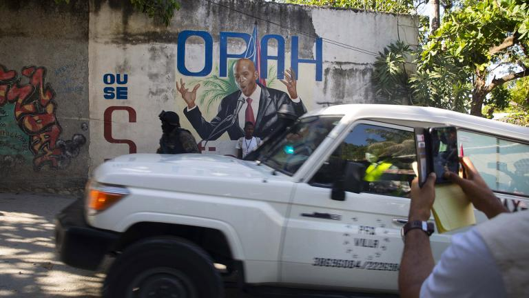 An ambulance carrying the body of Haiti's President Jovenel Moise drives past a mural featuring him near the leader's residence where he was killed by gunmen in the early morning in Port-au-Prince, Haiti, Wednesday, July 7, 2021. (AP Photo / Joseph Odelyn)