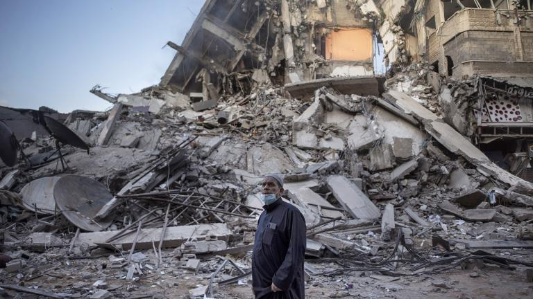 A Palestinian man looks at the destruction of a building hit by Israeli airstrikes in Gaza City, Thursday, May 13, 2021. (AP Photo / Khalil Hamra)