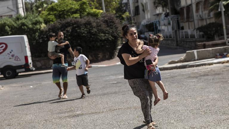 Lia Tal, 40, rushes with her children and partner to take shelter as a siren sounds a warning of incoming rockets fired from the Gaza Strip, In Ashdod, Israel, Thursday, May 20, 2021. (AP Photo / Heidi Levine)