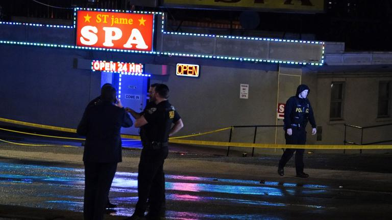 Law enforcement officials confer outside a massage parlor following a shooting on Tuesday, March 16, 2021, in Atlanta. (AP Photo / Brynn Anderson)