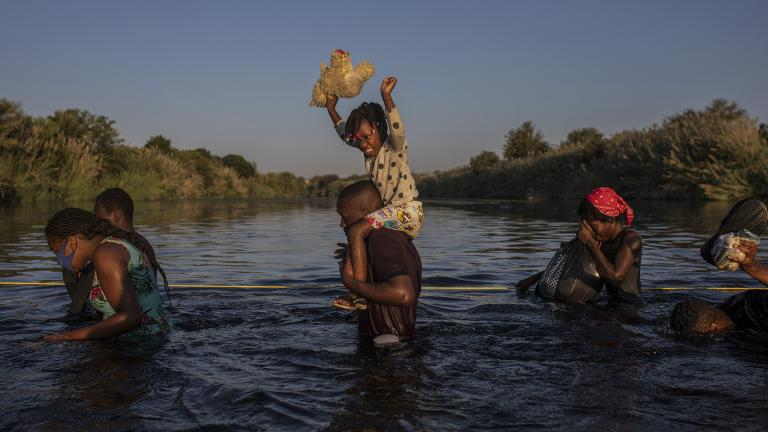 A little girl holds her stuffed animal high above the water as migrants, many from Haiti, wade across the Rio Grande river from Del Rio, Texas, to return to Ciudad Acuña, Mexico, Monday, Sept. 20, 2021, to avoid deportation. (AP Photo / Felix Marquez)