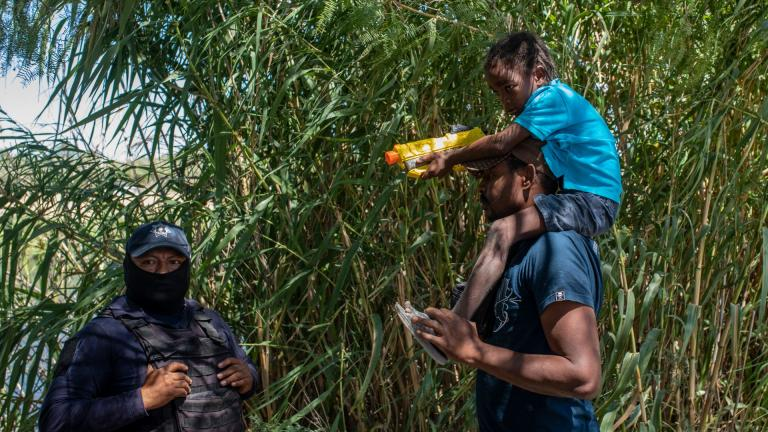 A Haitian migrant talks to with a Mexican police officer blocking access to the Rio Grande river so that immigrants can't use it to cross the U.S.-Mexico border from Ciudad Acuna, Mexico, Thursday, Sept. 23, 2021. (AP Photo / Felix Marquez)